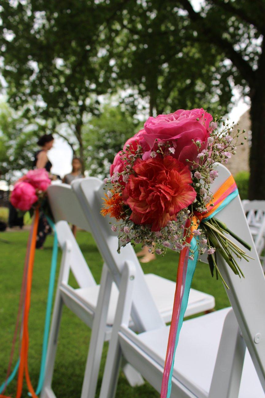 Blumen und Bänder in den Hochzeitsfarben an den Stühlen für das Brautpaar